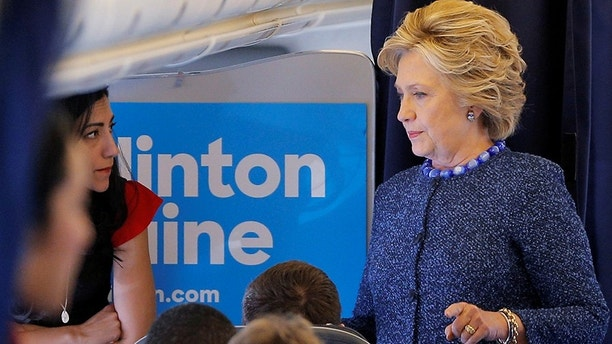U.S. Democratic presidential nominee Hillary Clinton talks to staff members, including aide Huma Abedin (L), onboard her campaign plane in White Plains, New York, U.S. October 28, 2016.  REUTERS/Brian Snyder  - S1AEUJQGXIAA
