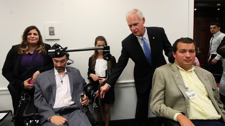 Sen. Ron Johnson, R-Wis., back right, reaches for the arms of ALS sufferers Frank Mongiello, left, and Matthew Bellina, during a news conference following the passage of the Right to Try Act at the Capitol in Washington.
