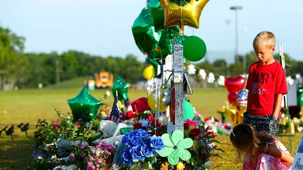 Two children look at a memorial for the Santa Fe High School shooting victims outside the school Wednesday, May 23, 2018, in Santa Fe, Texas. (Godofredo A. Vasquez /Houston Chronicle via AP)
