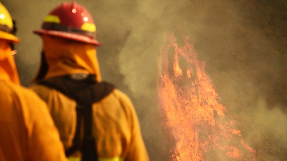Firefighters watch as flames consume pockets of unburned vegetation in Montecito, Calif., Dec. 13, 2017.