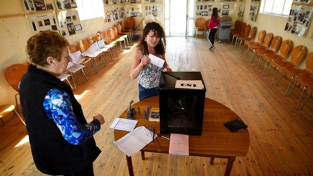 Presiding officer Carmel McBride looks on as a woman casts her vote in the referendum on the 8th Amendment of the Irish Constitution, on Thursday May 24, 2018, a day early for the people that live off the coast of Donegal on the island of Inishbofin, Ireland. The referendum on whether to repeal the country's strict anti-abortion law is being seen by anti-abortion activists as a last-ditch stand against what they view as a European norm of abortion-on-demand, while for pro-abortion rights advocates, it is a fundamental moment for declaring an Irish woman's right to choose. (Clodagh Kilcoyne/PA via AP)