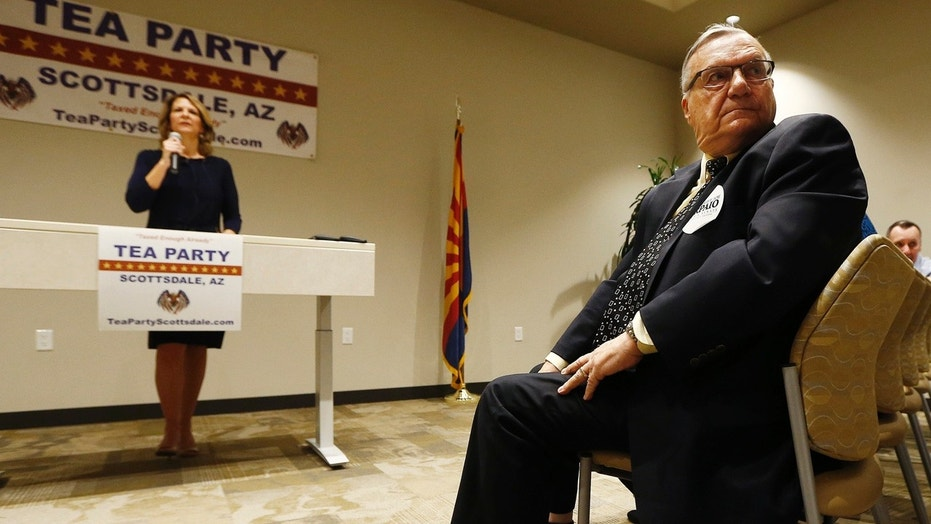 May 17: , Republican Senate candidates Kelli Ward, left, and former Maricopa Country Sheriff Joe Arpaio, right, listen to a question from the audience as the candidates talk about their platform policies at a Scottsdale Tea Party event.