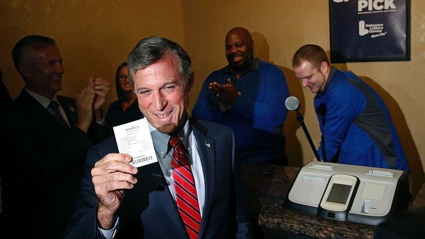Delaware Gov. John Carney displays a receipt for a bet he placed on a baseball game between the Chicago Cubs and the Philadelphia Phillies, Tuesday, June 5, 2018, inside the Race and Sports Book at Dover Downs Hotel and Casino in Dover, Del. The market for legal sports gambling in the United States widened significantly on Tuesday with the expansion of single-game sports bets in Delaware, less than a month after the U.S. Supreme Court cleared the way for states to accept the bets.