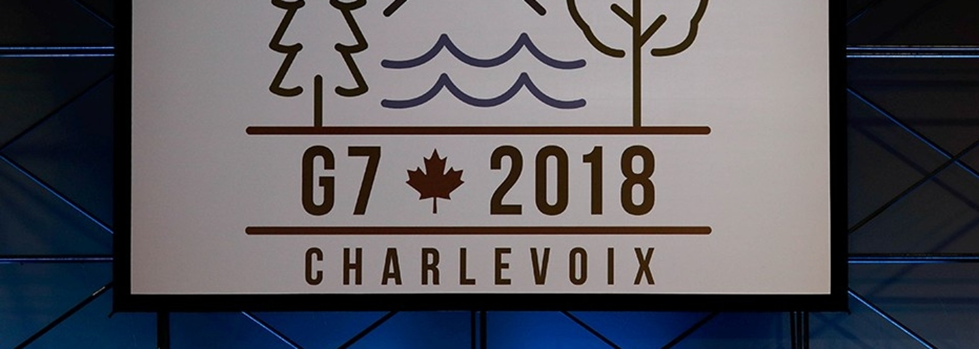 A Canadian mounted police officer walks past the Charlevoix G7 logo at the main press center, ahead of G7 Summit in Quebec, Canada June 6, 2018. REUTERS/Yves Herman - RC1D00D1D4F0