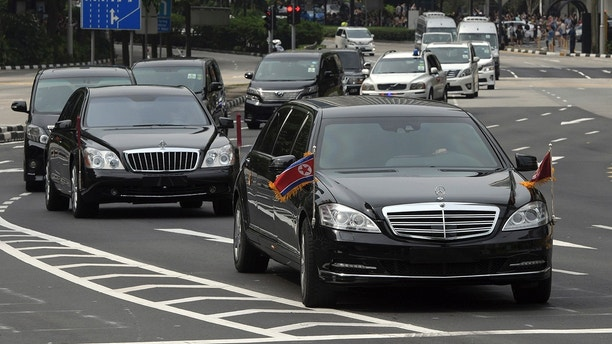 The North Korean motorcade, believed to be carrying North Korean leader Kim Jong Un, travels along Singapore's Orchard Road, Sunday, June 10, 2018, ahead of the summit with U.S. leader Donald Trump. (AP Photo/Joseph Nair)