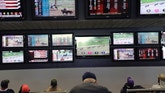 FILE - In this May 14, 2018, file photo, men watch horse racing on an array of screens at Monmouth Park Racetrack in Oceanport, N.J. New Jersey's proposed sports betting law is heading down to the wire, with final legislative approval expected on Thursday, June 7.  (AP Photo/Seth Wenig, File)