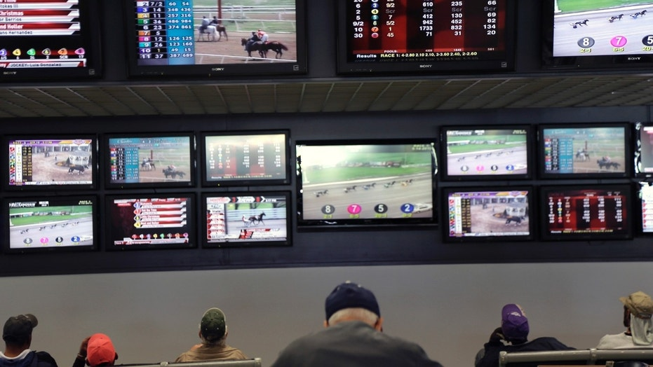 Men watch horse racing on screens at Monmouth Park in Oceanport, N.J.