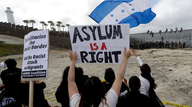Central American migrants sit on top of the border wall on the beach in San Diego during a gathering of migrants living on both sides of the border, Sunday, April 29, 2018. (AP Photo/Chris Carlson)