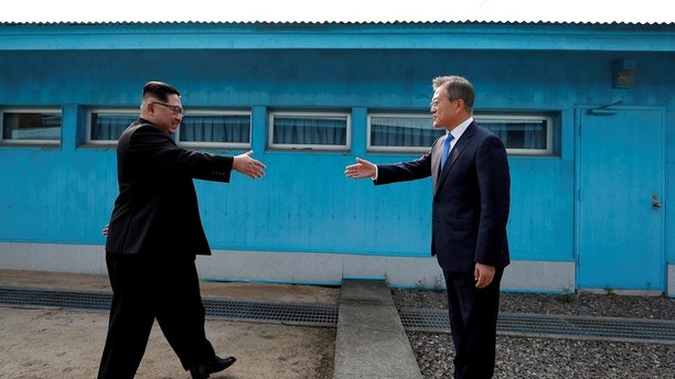 FILE PHOTO: South Korean President Moon Jae-in and North Korean leader Kim Jong Un (L) are about to shake hands on their first ever meeting at the truce village of Panmunjom inside the demilitarized zone separating the two Koreas, South Korea, April 27, 2018.  Korea Summit Press Pool via Reuters/File Photo - RC1B628D5710