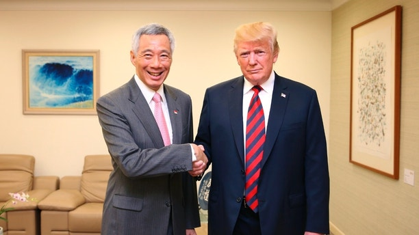 In this photo released by the Ministry of Communications and Information of Singapore, U.S. President Donald Trump, right,  and Singapore Prime Minister Lee Hsien Loong, left, shake hands in Singapore, ahead of a summit with North Korean leader Kim Jong Un, Monday, June 11, 2018. (Ministry of Communications and Information Singapore via AP)