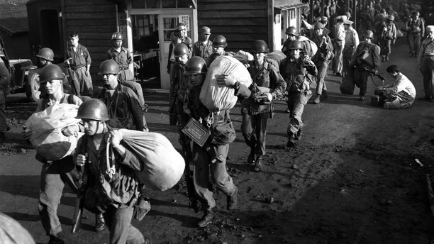 FILE - In this July 5, 1950, file photo, American foot soldiers leave the railroad station at Taejon, South Korea, en route to the battle front against North Korea. The most tangible outcome of the summit between President Donald Trump and North Korean leader Kim Jong Un seems to be a commitment to recover the remains of U.S. military personnel missing in action and presumed dead from the Korean War. In a joint statement signed by the leaders Tuesday, the countries committed to the recovery of the remains and the immediate repatriation of those already identified. (AP Photo)