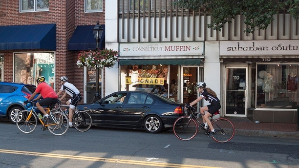 New Canaan, USA - July 22, 2012: Three bikers on one the streets located in the downtown business area in the town of New Canaan. The town beginnings was with the establishment of the Canaan Parish and today the town is one the wealthiest comunities in the country with a population of twenty thousand.