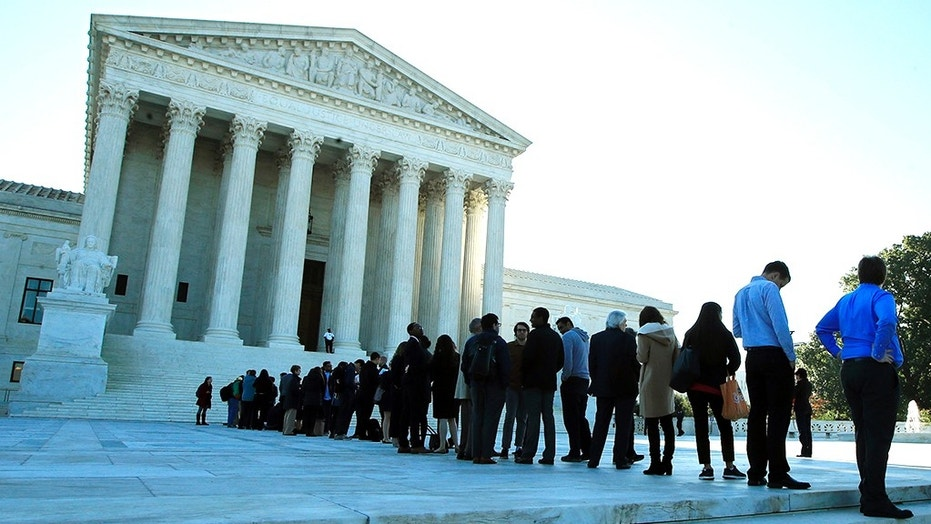 In this Oct. 3, 2017, file photo, people line up outside the U.S. Supreme Court in Washington to hear arguments in a case about political maps in Wisconsin