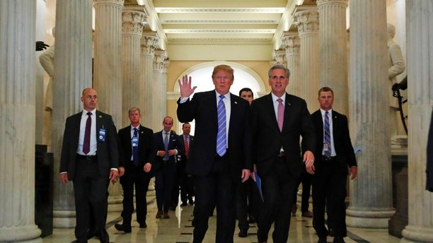 President Donald Trump, center, accompanied by House Majority Leader Kevin McCarthy of Calif., waves as he departs Capitol Hill in Washington, Tuesday, June 19, 2018, after a meeting to rally Republicans around a GOP immigration bill.  (AP Photo/Alex Brandon)