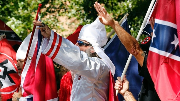 "In this Saturday, July 8, 2017 photo, Klan members salute during a KKK rally in Justice Park, in Charlottesville, Va. The number of Ku Klux Klan chapters in the U.S. is plummeting as a new generation of khaki-clad racists rejects hoods and robes for a ""hipper"" brand of hate, according to a report Wednesday by an organization that tracks far-right extremists. (AP Photo/Steve Helber)"