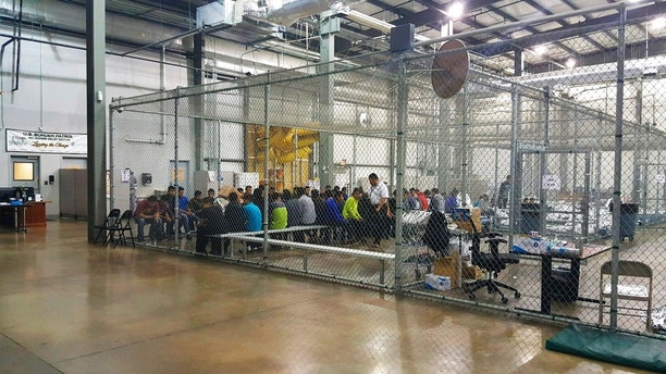 In this photo provided by U.S. Customs and Border Protection, people who've been taken into custody related to cases of illegal entry into the United States, sit in one of the cages at a facility in McAllen, Texas, Sunday, June 17, 2018. (U.S. Customs and Border Protection's Rio Grande Valley Sector via AP)