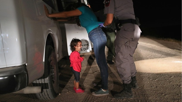 MCALLEN, TX - JUNE 12:  A two-year-old Honduran asylum seeker cries as her mother is searched and detained near the U.S.-Mexico border on June 12, 2018 in McAllen, Texas. The asylum seekers had rafted across the Rio Grande from Mexico and were detained by U.S. Border Patrol agents before being sent to a processing center for possible separation. Customs and Border Protection (CBP) is executing the Trump administration's zero tolerance policy towards undocumented immigrants. U.S. Attorney General Jeff Sessions also said that domestic and gang violence in immigrants' country of origin would no longer qualify them for political asylum status.  (Photo by John Moore/Getty Images)