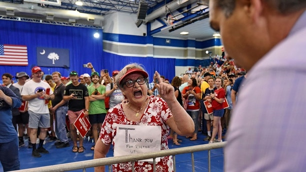 Maria Rojas, from West Columbia berates CNN Chief White House Correspondent Jim Acosta, right, before President Trump who is in town to support Gov. Henry McMaster speaks to the crowd at Airport High School Monday, June 25, 2018, in West Columbia, S.C. (AP Photo/Richard Shiro)