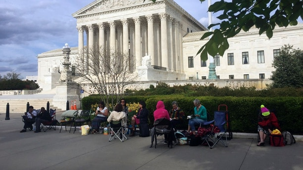 In this April 23, 2018, photo, people wait in line outside the Supreme Court in Washington, to be in the gallery when the court hears arguments in on April 25, over President Donald Trump's ban on travelers from several mostly Muslim countries. (AP Photo/Jessica Gresko)