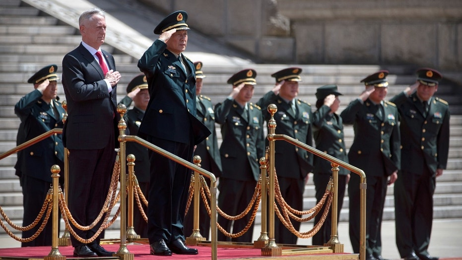 U.S. Defense Secretary Jim Mattis, front left, and China's Defense Minister Wei Fenghe stand as the American national anthem is played during a welcome ceremony at the Bayi Building in Beijing, Wednesday, June 27, 2018.