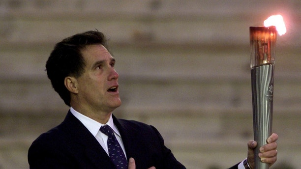 President of the organising committee of Salt Lake Winter Olympic Games Mitt Romney sings U.S. national anthem as he raises an Olympic torch December 3, 2001, during a handing-over ceremony in Athens' Panathenean stadium. The flame will travel 13,500 miles across the United States in 65 days and will arrive in Salt Lake's Olympic stadium on February 8, 2001. REUTERS/Yiorgos Karahalis  YK/GB - RP2DRIQSROAB