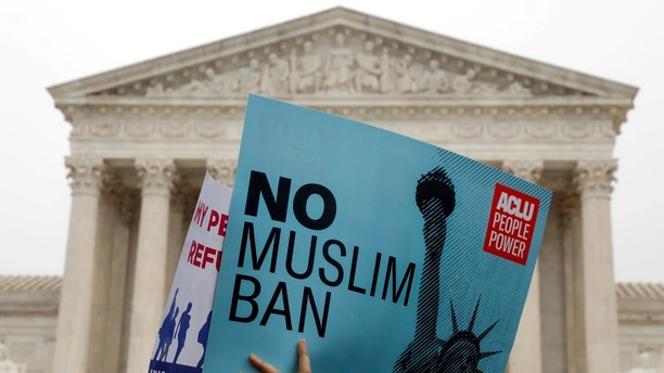 Protesters rally outside the U.S. Supreme Court, while the court justices consider case regarding presidential powers as it weighs the legality of President Donald Trump's latest travel ban targeting people from Muslim-majority countries, in Washington, DC, U.S., April 25, 2018. REUTERS/Yuri Gripas - RC11BDE4C3E0