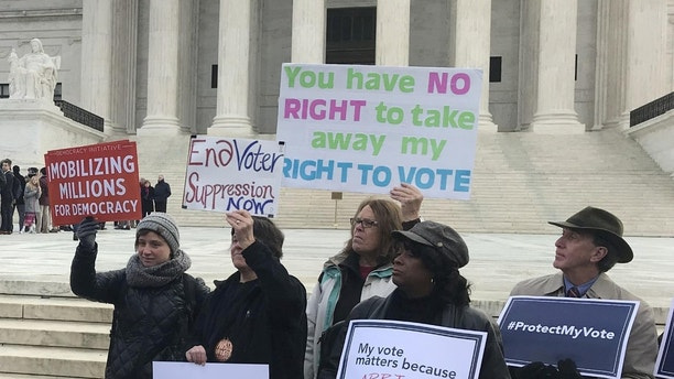 Activists rally outside the U.S. Supreme Court ahead of arguments in a key voting rights case involving a challenge to the OhioÕs policy of purging infrequent voters from voter registration rolls, in Washington, U.S., January 10, 2018. REUTERS/Lawrence Hurley - RC1A0EBC60B0