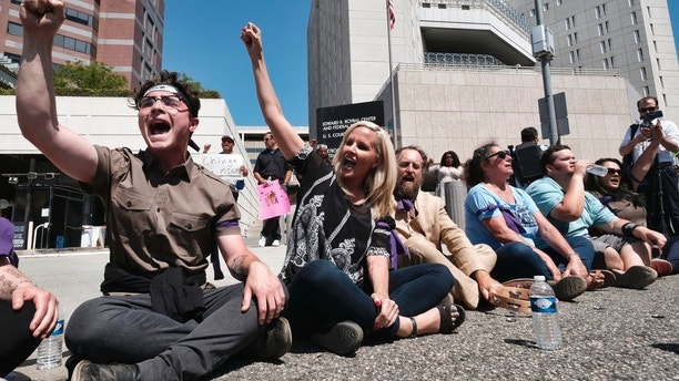 """Protesters chant slogans and stage a sit-in before being arrested in front of the Immigration and Customs Enforcement facility in downtown Los Angeles on Monday, July 2, 2018. The protesters, including faith and community leaders, locked arms and chanted, """"Shut down ICE!"""" (AP Photo/Richard Vogel)"""
