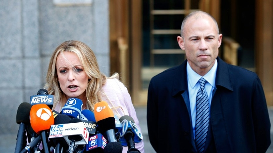 Michael Avenatti looks on as Stormy Daniels speaks to the media outside federal court in Manhattan this past April.