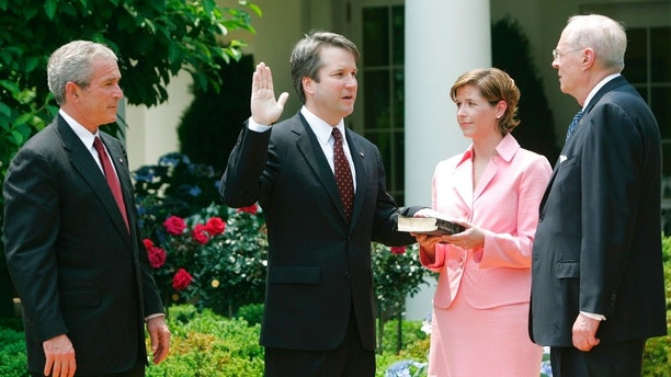 FILE - In this June 1, 2006 file photo, from left to right, President Bush, watches the swearing-in of Brett Kavanaugh as Judge for the U.S. Court of Appeals for the District of Columbia by U.S. Supreme Court Associate Justice Anthony M. Kennedy, far right, during a ceremony in the Rose Garden of the White House, in Washington. Holding the Bible is Kavanaugh's wife Ashley Kavanaugh. Kavanaugh is one of four judges thought to be President Donald Trump's top contenders to fill a vacancy on the Supreme Court.  (AP Photo/Pablo Martinez Monsivais, File)