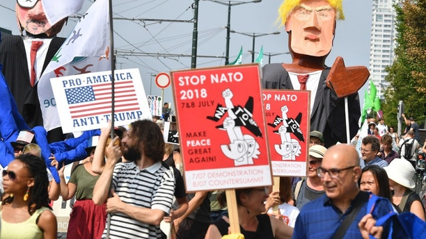 Protestors march next to giant puppets of U.S. President Donald Trump, right, and Belgian Prime Minister Charles Michel, left, during a demonstration in Brussels, Saturday, July 7, 2018. European activists are protesting U.S. President Donald Trump's upcoming appearance at a NATO summit, marching through Brussels to plead for less military spending and more public money for schools and clean energy. (AP Photo/Geert Vanden Wijngaert)