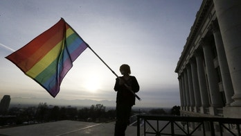 Corbin Aoyagi, a supporters of gay marriage, waves his flag during a rally at the Utah State Capitol, Tuesday, Jan. 28, 2014, in Salt Lake City. Opponents and supporters of gay marriage held twin rallies at the Capitol on Tuesday. More than 1,000 gay couples rushed to get married when a federal judge overturned Utah's constitutional amendment banning same-sex marriage in late December 2013. In early January the U.S. Supreme Court granted Utah's request for an emergency halt to the weddings. (AP Photo/Rick Bowmer)