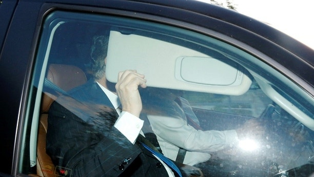 Former Trump campaign manager Paul Manafort, one focus of special counsel Robert Mueller's investigation into alleged Russian meddling in the 2016 U.S. presidential election, hides behind his car visor as he leaves his home in Alexandria, Virginia, U.S. October 30, 2017. REUTERS/Jonathan Ernst - RC1F89D175A0