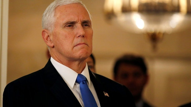 FILE PHOTO:    U.S. Vice President Mike Pence listens to U.S. President Donald Trump (not pictured) speak about the mass shooting at a Florida high school in a national address from the White House in Washington, U.S., February 15, 2018. REUTERS/Leah Millis/File Photo - RC193F92DD90