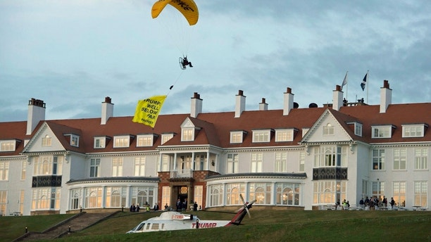 "In this Friday, July 13, 2018 photo, a Greenpeace protester flying a microlight passes over US President's Donald Trump's resort in Turnberry, South Ayrshire, Scotland with a banner reading ""Trump: Well Below Par"", shortly after the US President arrived at the hotel. Scottish police said the protester breached a no-fly zone over Turnberry hotel and committed a criminal offence. ( John Linton/PA via AP)"