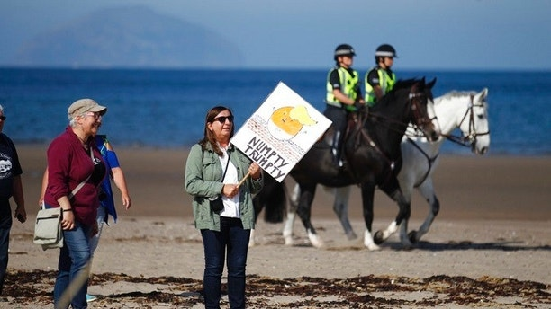 Protesters arrive on a beach near Turnberry golf club, in Turnberry,  Scotland, Saturday, July 14, 2018. U.S. President Donald Trump  has tweeted that he will hopefully have time to play golf during his visit to Scotland. (AP Photo/Peter Morrison)