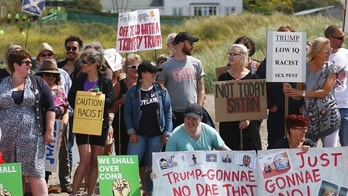 Protesters on a beach near Turnberry golf club, Scotland, Saturday, July 14, 2018. U.S. President DonaldTrump is due to play golf at his Turnberry course Saturday. (AP Photo/Peter Morrison)