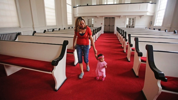 In this May 31, 2018, photo, Vicky Chavez walks with her daughter Issabella in the First Unitarian Church, in Salt Lake City. Chavez, a Honduran woman who came to the U.S. four years ago seeking asylum from an abusive boyfriend says she'll continue taking sanctuary in a Salt Lake City Unitarian church where she's been for the past six months with her two young daughters despite being ordered to leave and exhausting her appeals. (AP Photo/Rick Bowmer)