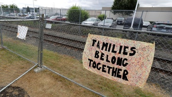 """FILE - In this July 10, 2018, file photo, a sign that reads """"Families belong Together"""" hangs on a fence outside the Northwest Detention Center in Tacoma, Wash. Immigration Judge John G. Crews on Monday, July 16, 2018, declined to release Salvadoran mother, Blanca Orantes-Lopez, from the detention center citing new and more restrictive guidelines on asylum seekers from Attorney General Jeff Sessions. (AP Photo/Ted S. Warren, file)"""
