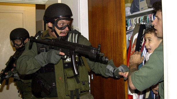FILE - In this April 22, 2000, file photo, by Associated Press photojournalist Alan Diaz, Elian Gonzalez is held in a closet by Donato Dalrymple, one of the two men who rescued the boy from the ocean, right, as government officials search the home of Lazaro Gonzalez for the young boy, in Miami.  Retired Associated Press photojournalist Alan Diaz, whose photo of the terrified 6-year-old Cuban boy named earned him the Pulitzer Prize, died Tuesday, July 3, 2018, his daughter Aillette Rodriguez-Diaz said. He was 71. (AP Photo/Alan Diaz, File)
