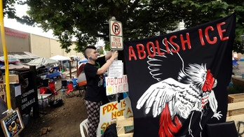 FILE - In this June 25, 2018, file photo, a woman, who would not identify herself, hangs a sign at a protest camp on property outside the U.S. Immigration and Customs Enforcement office in Portland, Ore. Supporters of Initiative Petition 22, which would repeal the sanctuary status, turned in enough voter signatures last week to put them within reach of having the question put to voters and are waiting to see if the petition will qualify for the November ballot. (AP Photo/Don Ryan, File)