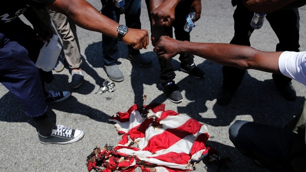 People place their fists over a burned U.S. flag as they chant slogans outside the Los Angeles office of U.S. Rep. Maxine Waters, Thursday, July 19, 2018, in Los Angeles. A crowd gathered at the field office to counter a protest by a self-styled militia group burned the flag taken from the back of a pickup truck that drove up to the scene. The pickup, with two men who appeared to be white inside, was stopped by the crowd. The crowd opened the doors and a man then grabbed the flag flying on a pole in the bed of the vehicle, which took off. (AP Photo/Jae C. Hong)