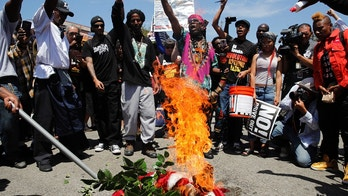 People chant slogans as they burn a U.S. flag outside the Los Angeles office of U.S. Rep. Maxine Waters, Thursday, July 19, 2018, in Los Angeles. A crowd gathered at the field office to counter a protest by a self-styled militia group burned the flag taken from the back of a pickup truck that drove up to the scene. (AP Photo/Jae C. Hong)