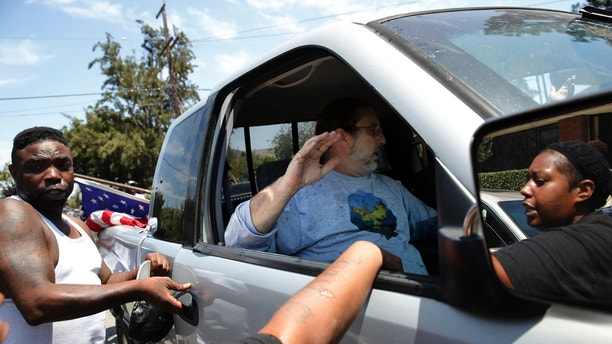 People in a counter-protest try to open the door of a pickup truck occupied by two men outside the Los Angeles office of U.S. Rep. Maxine Waters, Thursday, July 19, 2018, in Los Angeles. The crowd of counter-protesters were gathering at the field office of Waters, a black Democrat who has made comments criticizing President Donald Trump, to counter a protest by a self-styled militia group. The incident happened Thursday after the Oath Keepers group didn't appear to protest at Waters' office. (AP Photo/Jae C. Hong)