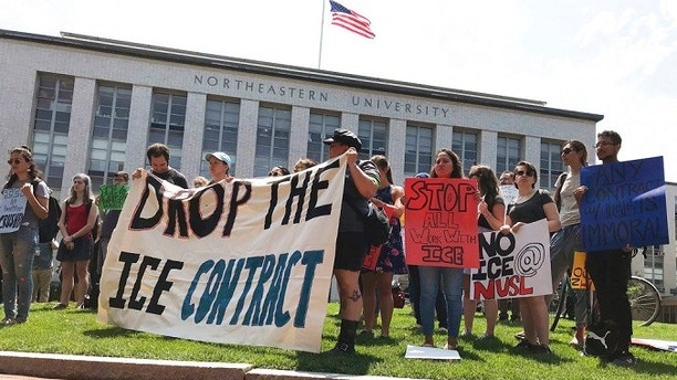 FILE - In this July 11, 2018 file photo, students and community activists rally at Northeastern University in Boston demanding the school cancel a multimillion-dollar research contract with U.S. Immigration and Customs Enforcement. Northeastern was hired by ICE to research U.S. technology exports. Several colleges with ties to ICE are being pressured to split with the agency amid uproar over the separation of migrant families along the nation's border. (AP Photo/Sarah Betancourt, File)