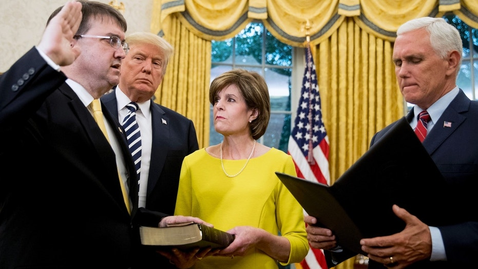 Vice President Mike Pence administers the oath of office to new VA Secretary Robert Wilkie as President Donald Trump and Wilkie's wife Julia look on.