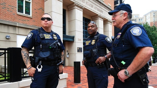 Security personnel from the Department of Homeland Security's Federal Protective Service, watch the vicinity around the Alexandria Federal Court in Alexandria, Va., on day one of Paul Manafort's trial, Tuesday, July 31, 2018. (AP Photo/Manuel Balce Ceneta)