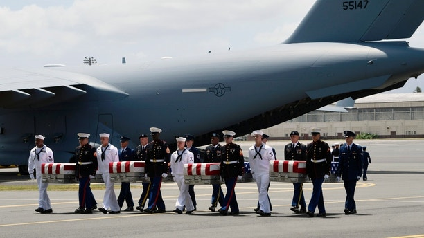 Military members carry transfer cases from a C-17 at a ceremony marking the arrival of the remains believed to be of American service members who fell in the Korean War at Joint Base Pearl Harbor-Hickam in Hawaii, Wednesday, Aug. 1, 2018. North Korea handed over the remains last week. (AP Photo/Susan Walsh)