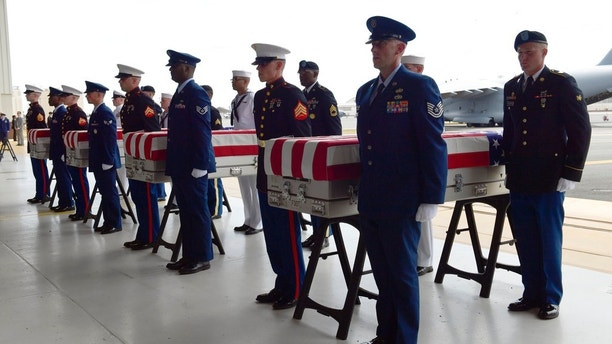 Military members stand at attention after placing transfer cases in a hanger at a ceremony marking the arrival of the remains believed to be of American service members who fell in the Korean War at Joint Base Pearl Harbor-Hickam in Hawaii, Wednesday, Aug. 1, 2018. North Korea handed over the remains last week. (AP Photo/Susan Walsh)