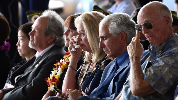 Robert Sanfilkippo, second right, sits next to his wife, Diana Brown Sanfilippo who has spent a lifetime searching for her father, 1st Lt. Frank Salazar who died 66 years ago in North Korea, who wipes her eyes as she sits in the audience with Karen Pence, wife of Vice President Mike Pence, at a ceremony marking the arrival of the remains believed to be of American service members who fell in the Korean War at Joint Base Pearl Harbor-Hickam, Hawaii, Wednesday, Aug. 1, 2018. North Korea handed over the remains last week. Second from left is Rick Downes, who was three when his father Hal went off to the Korean War, and he has been missing ever since. (AP Photo/Susan Walsh)